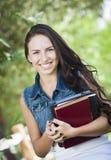 混合的族种有教科书的女孩学员 免版税图库摄影