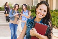 混合的族种有教科书的女孩学生在校园里 免版税库存图片