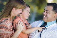 混合的族种男孩、母亲和Having Fun With Stethoscope医生 库存图片