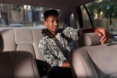 混合的族种的一个愉快的人,在汽车进来,拿着一把吉他,充满心情,户内汽车的图象 免版税图库摄影