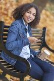 混合的族种非裔美国人少年妇女咖啡发短信 免版税图库摄影