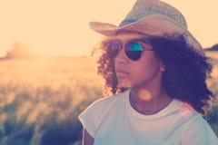 混合的族种非裔美国人的妇女太阳镜牛仔帽日落 免版税库存图片