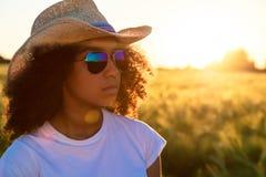 混合的族种非裔美国人的妇女太阳镜牛仔帽日落 免版税库存照片
