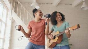 混合的族种年轻滑稽的女孩跳舞唱歌与hairdryer和弹在床上的声学吉他 有的乐趣姐妹 股票录像
