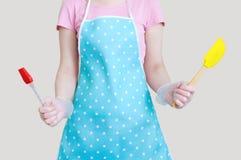 混合的硅树脂小铲提取乳脂和点心 在女性手上 白色孤立 库存图片