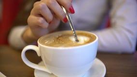 混合的糖到一个杯子拿铁咖啡里,慢动作 妇女` s的特写镜头递混合的糖和咖啡在白色 股票视频