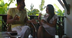 混合种族夫妇谈的坐夏天大阳台饮用的汁液、愉快的人和妇女通信 影视素材