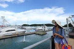 混合种族晒黑了皮肤沿豪华游艇的妇女步行在小游艇船坞Ba 免版税库存图片