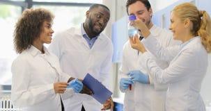 混合种族科学家队在瓶在实验的愉快的微笑的Reseachers谈论液体在实验室 股票视频
