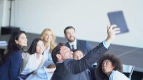 混合赛跑的小组商人拍在片剂计算机上的Selfie照片在颁奖大会队期间做自已 股票视频