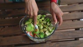 混合鳄梨调味酱捣碎的鳄梨酱的女性手特写镜头产品在桌上在家庭厨房里 股票录像
