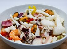 混杂的地中海海鲜沙拉白色盘在木桌上的 免版税库存照片