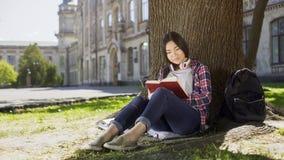 混杂的女性开会在树,读书喜爱的书,扣人心弦的剧情下,大字书写 免版税库存图片