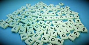 混杂的拼字游戏瓦片暗藏的消息 免版税库存照片