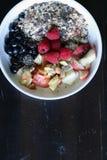 混杂的果子和谷物在一个白色碗在棕色木桌上 库存图片