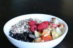 混杂的果子和谷物在一个白色碗在棕色木桌上 免版税库存照片