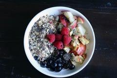 混杂的果子和谷物在一个白色碗在棕色木桌上 图库摄影