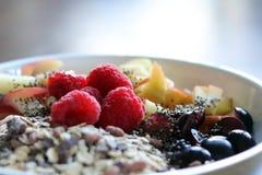 混杂的果子和谷物在一个白色碗在棕色木桌上 免版税图库摄影