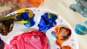 混杂的油漆和油漆盖了在油漆调色板的油漆刷 免版税库存图片