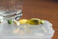 混杂的自然食物补充和维生素药片在塑胶容器在木桌上 免版税库存图片