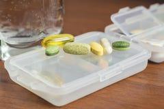 混杂的自然食物补充和维生素药片在塑胶容器在木桌上 免版税库存照片