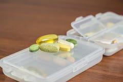 混杂的自然食物补充和维生素药片在塑胶容器在木桌上 图库摄影