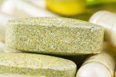 混杂的自然食物补充药片、多种维生素片剂和氨基葡萄糖胶囊,宏观图象 库存图片