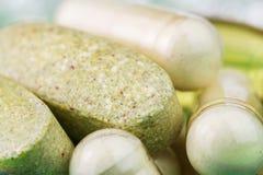 混杂的自然食物补充药片、多种维生素片剂和氨基葡萄糖胶囊,宏观图象 免版税库存照片