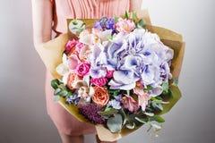 混杂的花美丽的豪华花束在妇女手上 卖花人的工作在花店 免版税库存图片