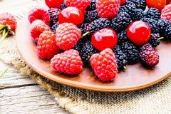 混杂的莓果莓、樱桃、桑树在一个碗在粗麻布和木背景 免版税库存图片