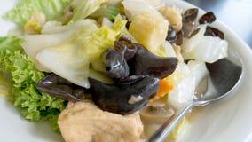 混杂的菜在黑桌背景的白色板材混乱油煎了 免版税库存图片