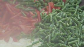 混杂的裁减红色和绿色菜在煮沸被搅动并且被炖液体调味汁 影视素材