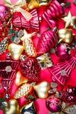 混杂的金黄和红色圣诞节装饰品一张顶视图在红色背景的 库存照片