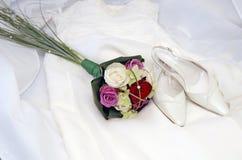 混杂的颜色玫瑰花束、白色鞋子和婚礼礼服 免版税库存图片