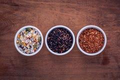 混杂的整个在匙子和碗的五谷传统泰国米是 免版税库存图片