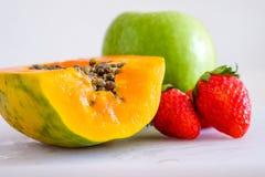 混杂的cutted果子woth番木瓜、strawberrt和苹果 免版税图库摄影