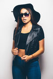 混血儿女孩佩带的太阳镜和黑帽会议在白色背景 免版税库存照片