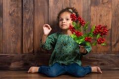 混血儿女孩用莓果在她的手上 免版税图库摄影