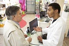 年轻混血儿男性药剂师讲话与顾客 免版税图库摄影