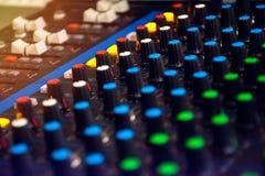 混音器在黑暗的轻的背景的控制板 免版税库存图片