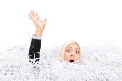 淹没在堆的女实业家切细的纸 免版税库存照片