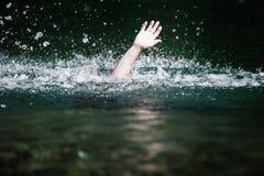 淹没的某人的手和需要帮助 免版税库存图片