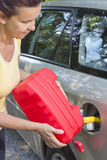 添加在汽车的中间变老的妇女燃料 免版税库存图片