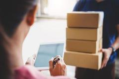 添附署名在数字片剂和接受纸板箱小包的妇女顾客从送货服务传讯者,家 免版税库存照片