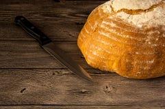 添面包和在一张木桌上的一把刀子 免版税库存照片