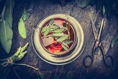 清凉茶、老剪刀和贤哲叶子在黑暗的土气木背景,顶视图 库存图片