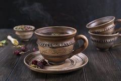 清凉茶、草本和花在黏土杯子在木桌上 库存照片
