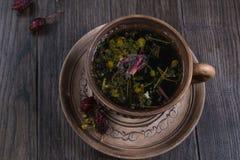 清凉茶、草本和花在黏土杯子在木桌上 免版税库存图片