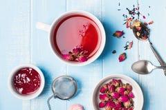 清凉茶和干燥玫瑰在蓝色颜色表上 图库摄影
