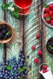 清凉茶和莓果在绿色土气桌上 免版税库存图片